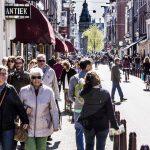 Mensen in de Spiegelstraat in het centrum van Amsterdam met in de verte het Rijksmuseum